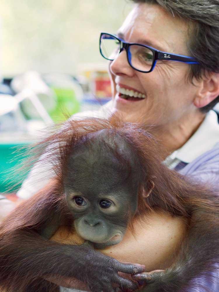 笑顔のローレン・マッコールと抱きかかえられているオランウータンの写真